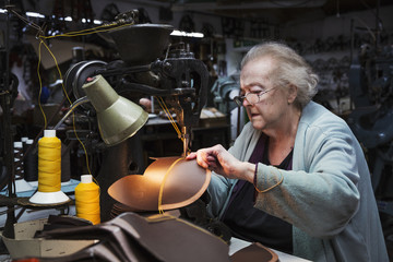 A grey haired senior worker of over 80 years old, a woman sitting at a sewing machine in a shoemaker's workshop.