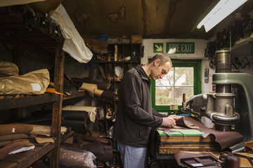 Man standing in a shoemaker's workshop, cutting brown leather.