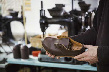 Man standing in a shoemaker's workshop, holding brown leather shoe.