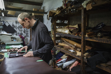 Man standing in shoemaker's workshop, cutting brown leather