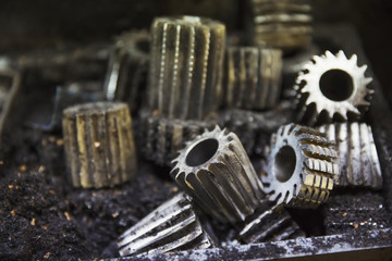 Close up of various shaped metal cogs and threads in a shoemaker's workshop.