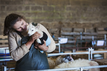 Woman standing in a barn, holding a newborn lamb dressed in a knitted jumper.