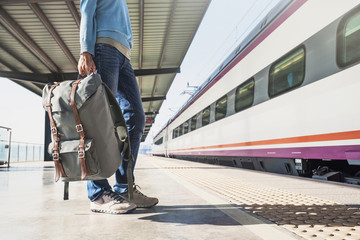 Young woman traveler waiting for a train on a railroad station, travel and active lifestyle concept