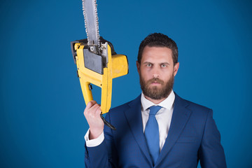 chainsaw in hand of young man, businessman or business worker