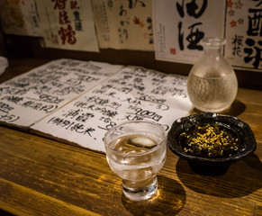 Traditional japanese sake and seaweed. Japanese menu and sake brands in the background.