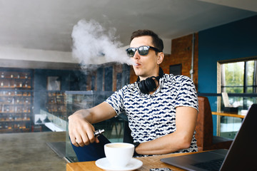 Young handsome hipster man insunglasse sitting in cafe with a cup of coffee, vaping and releases a cloud of vapor. Working at laptop and having a little break. With copy space.