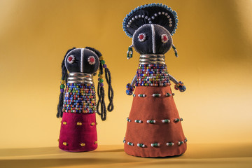 African cloth dolls isolated on yellow background