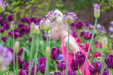 Little blonde girl smelling flowers in garden