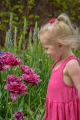 little girl standing in spring garden looking at flower blooms