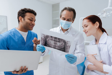 Attentive dentist in mask standing between interns