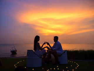 Romantic couple enjoying glass of wine against a beautiful sunset. Love and holiday concept.