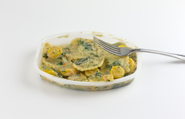 Ravioli with spinach TV dinner with a fork on the tray atop a white tablecloth.