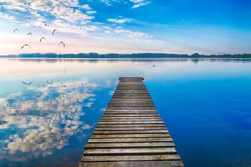 EBirds fly over empty footbridge. The lake Selment Wielki, Masuria, Poland.