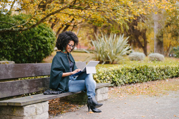 Stylish black female entrepreneur working with modern convertible laptop outdoor in autumn at city park. Young professional woman outside using tablet. Wall mural