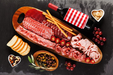Italian snacks on a black stone background. Meat sliced, delicatessen, wine. Fresh ciabatta bread