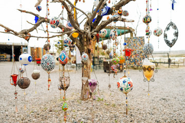 colorful Arabian ornaments hanging on a dying tree with white background. The objects are commercial to be sold to customers from business owner. Buyer can use for any decoration in their home.