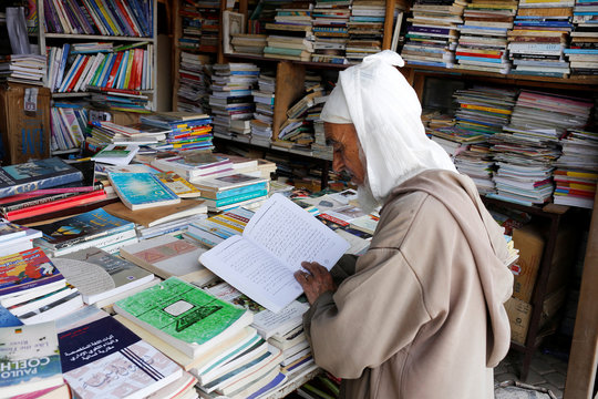 An elderly man reads a book in a bookshop in Bab Doukkala in the city of Marrakech