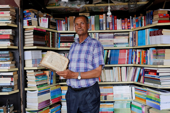 Bookseller Abdelaziz Ahlij holds a 100-year-old handwritten manuscript in his bookshop in Bab Doukkala in the city of Marrakech