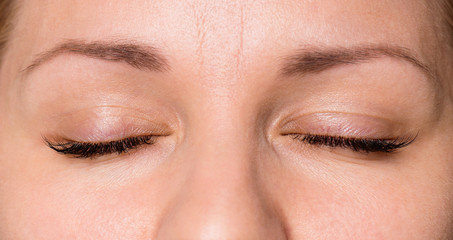 Close-up face of beautiful young woman with beautiful big eyelashes and eyebrows. Macro of human eye - close.