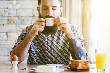 bearded man with breakfast and cup of morning coffee