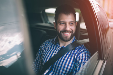 Beautiful man smiling while sitting on back seat in the car Wall mural
