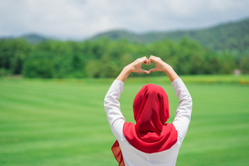 Portrait of happy young muslim red hijab at the green field.