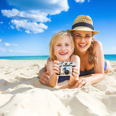 smiling mother and child on beach with retro photo camera