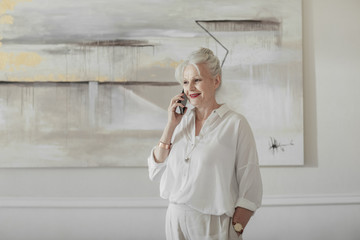 Beautiful senior Caucasian woman standing at home and talking on cell phone.