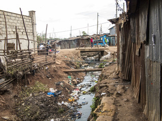 Open sewer and tin shacks in a slum in Africa