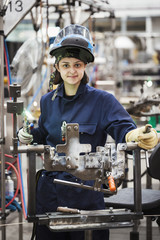 Female skilled factory worker holding welding tool, working on cycle frames