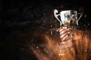 low key image of a man holding a trophy cup over dark background