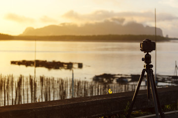 Camera set on a tripod aimed at a silhouette of a landscape at sunrise.