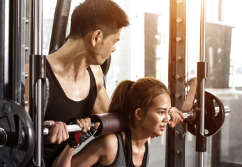 Personal trainer with girl on training weight-lifting workout in fitness center.