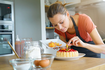 Young woman in domestic kitchen baking raspberry cake