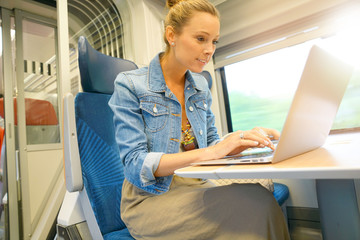 Young woman in train connected on laptop computer