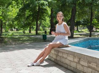 Young beautiful girl in short white dress sit near fountain