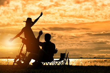 Silhouette Couple in Love of Man and Woman Enjoy Camping Near The Lake with Sunset Sky in Holiday Summer