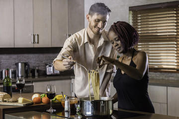 dinner preparation  kitchen cooking happy young mixed race couple
