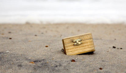 Small wooden treasure chest with metal clasp embedded in beach sand.