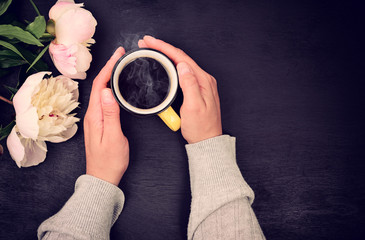 Cup of coffee in female hand on black background