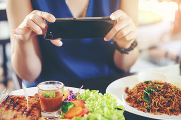 Close-up Woman's hands use pointing finger Mobile smart Phone on Food table, technology and home concept