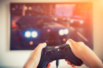 Player playing console car race videogame holding gamepad