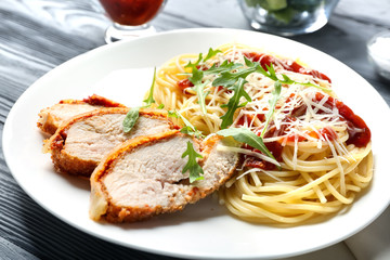 Tasty pasta with chicken parmesan slices and herbs on plate