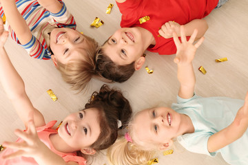 Cute little children with confetti lying on floor at home