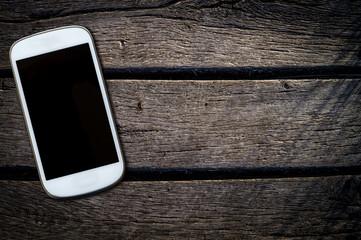 weisses mobiltelefon auf einem alten holztisch