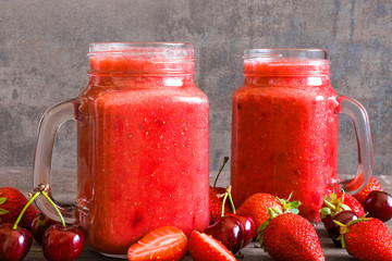 strawberry and cherry smoothie in glass jar with fresh fruits