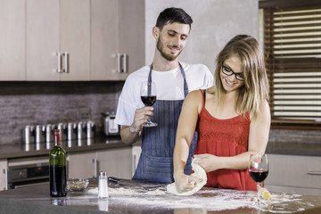Happy couple kneading dough together in kitchen