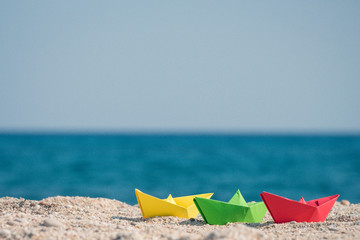 Paper boats in different colors on sandy beach