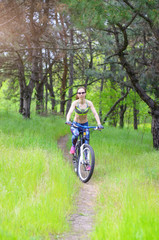 A young woman is riding a bicycle on a forest trail. Slender girl rides a bicycle, active rest.