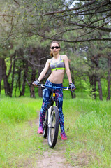 Young girl with bicycle on a forest path. Slender woman posing with bicycle, summer photo.